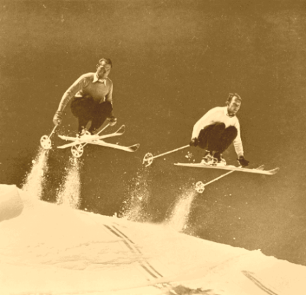 2_skiers_catching_air_on_vintage_skis